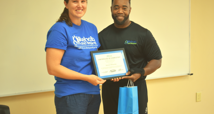 Two Rehabilitative Therapists, one male and one female, from Rehab and Beyond Non-profit Stand together holding National Stroke and Brain Injury Continuum Care Certification that female therapists has recently earned